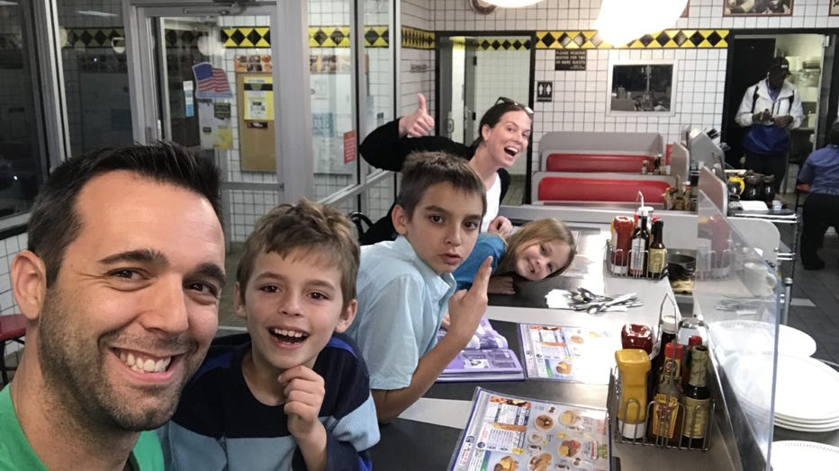 Family smiles and gestures at the camera while sitting at the counter of a Waffle House. The father is holding the camera and they have 3 children smiling between him and the mother, who is waving in the background.