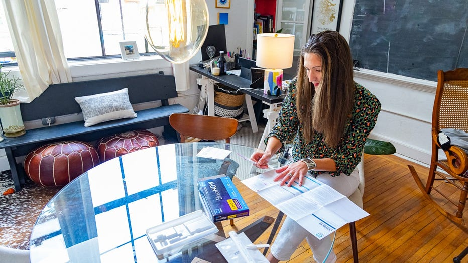 Woman with long brown hair sits at a round glass table in her loft apartment, reading the instructions of an at-home COVID-19 test kit. She's holding the nasal swab in her hand.