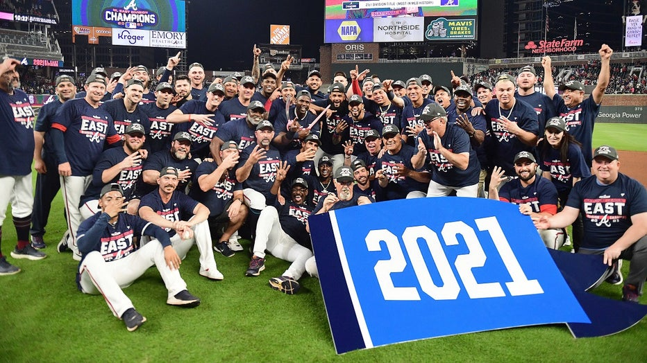 The Atlanta Braves celebrate after winning the NL Eastern Division against the Philadelphia Phillies at Truist Park on September 30, 2021 in Atlanta, Georgia. (Photo by Adam Hagy/Getty Images)