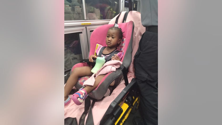 Little girl sits in car seat strapped to a gurney in the back of an ambulance.