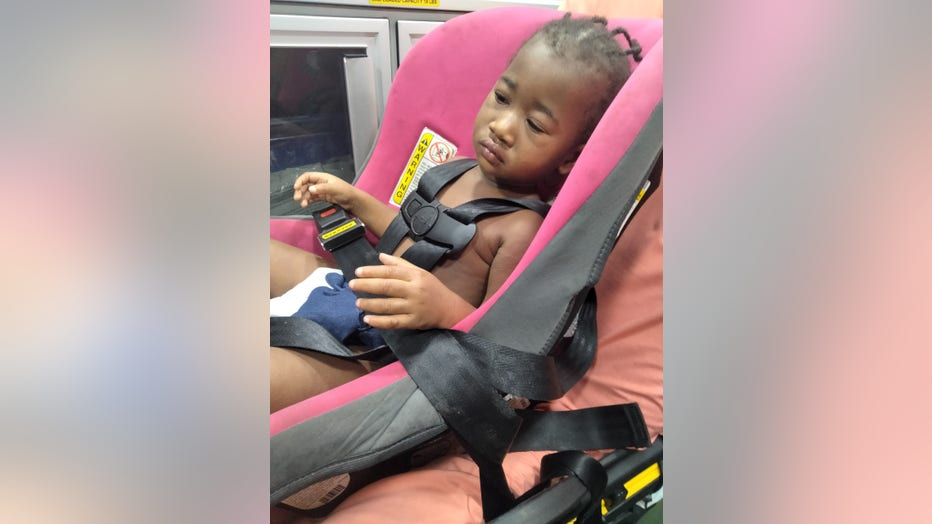 African American toddler sits in a car seat strapped to a gurney in the back of an ambulance.