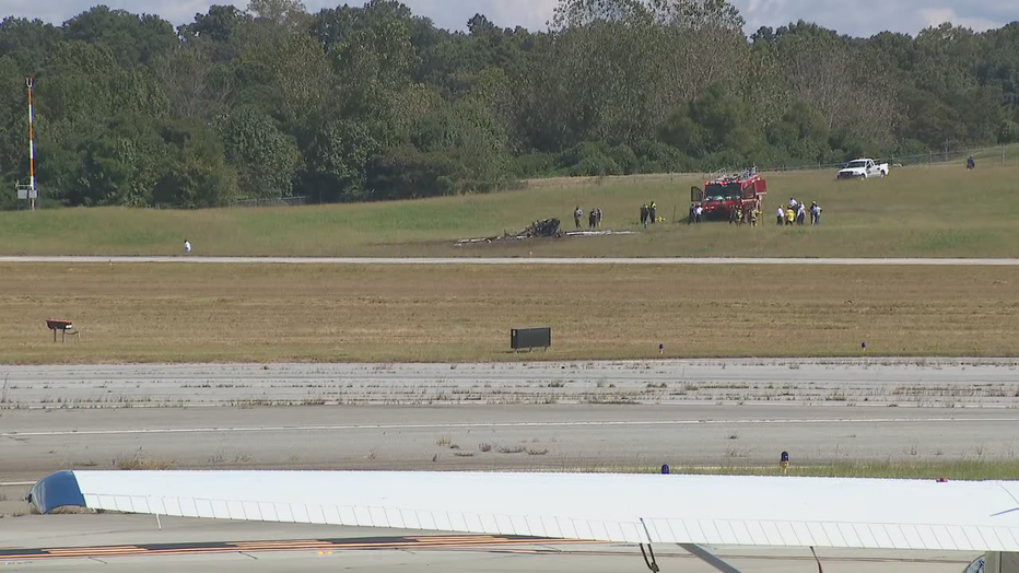 Firefighters inspect the wreckage of a burnt plane at DeKalb-Peachtree Airport on October 8, 2021.
