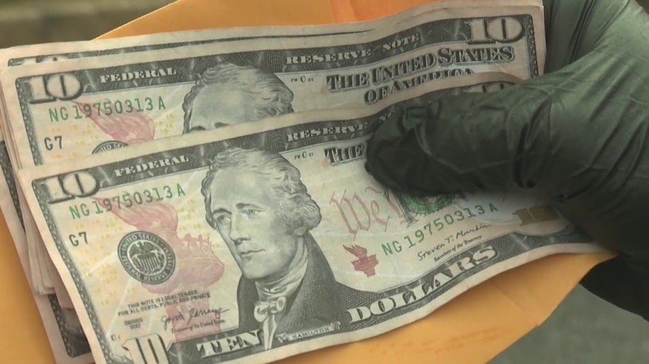 Athens police show two ten-dollar bills with the same serial number used at an area Walmart.