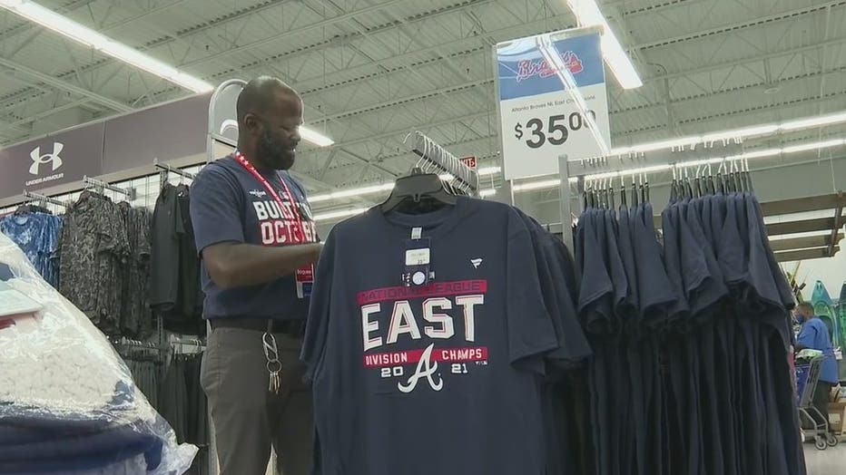 An employee at Academy Sports and Outdoors restocks Braves merchandise after the fourth-straight NL East Title on Oct. 1, 2021.