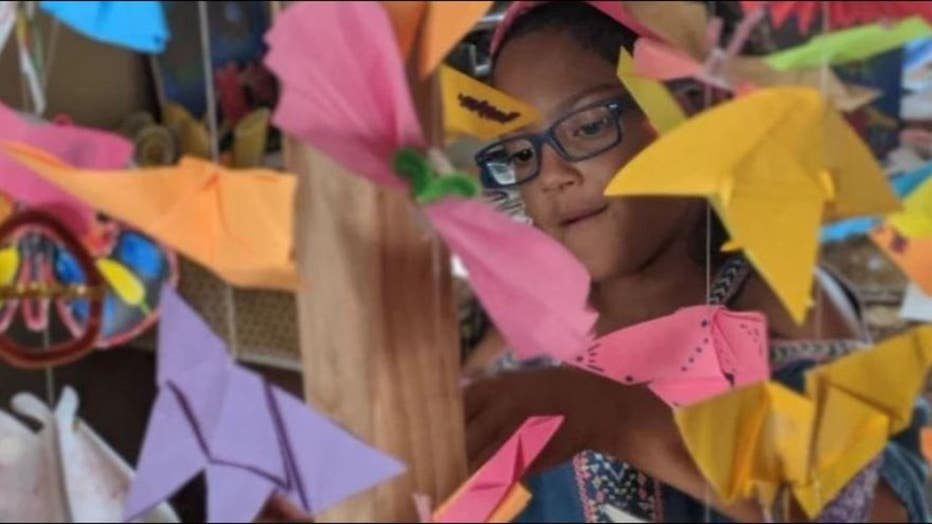 Lily Ellis, 10, stands with homemade butterflies to represent migrant children in U.S. detention facilities. Her goal, along with friend, Kaia Marbin, 11, is to create 15,000.
