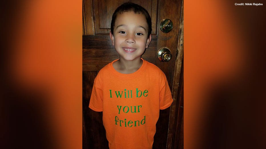 Blake, 6, is shown wearing his custom T-shirt that is orange with bright green letters that say