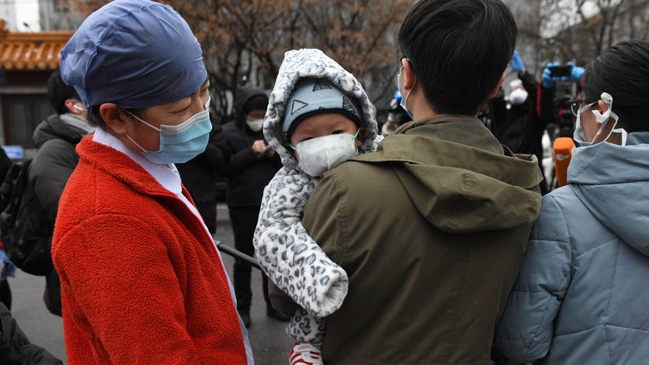 A nurse (L) looks at a 1-year-old boy as his father and mother (R) speak to the media during a ceremony marking their release after recovering from the COVID-19 coronavirus at the Youan Hospital in Beijing on Feb. 14, 2020. (Photo by GREG BAKER/AFP via Getty Images)