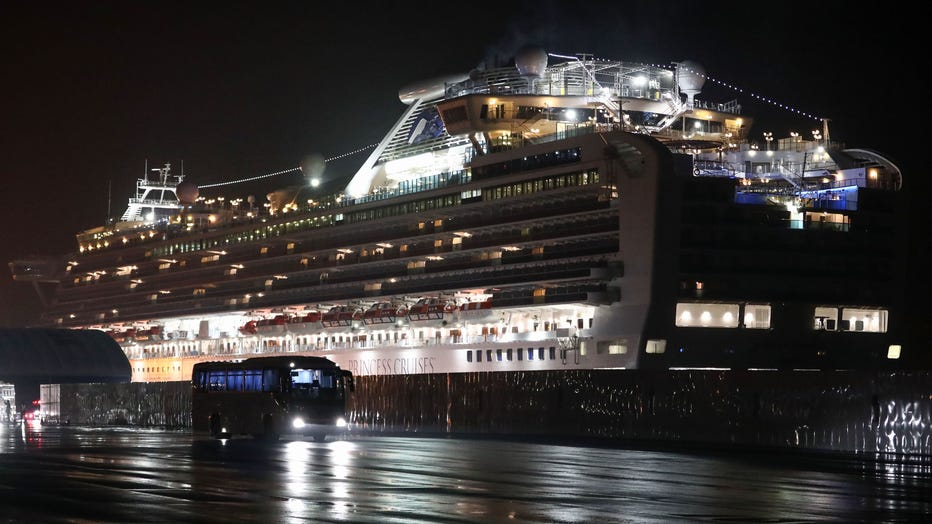 A bus carrying U.S. citizens leaves the Daikaku Pier Cruise Terminal in Yokohama port, next to the Diamond Princess cruise ship, with people quarantined onboard due to fears of the new COVID-19 coronavirus, on Feb. 17, 2020. (Photo by BEHROUZ MEHRI/AFP via Getty Images)