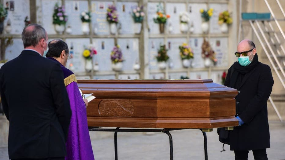 A man wearing a face mask stands by the coffin of his mother during a funeral service in the closed cemetery of Seriate, near Bergamo, Lombardy, on March 20, 2020 during the country's lockdown aimed at stopping the spread of the COVID-19 pandemic.