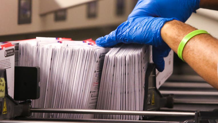 An election worker handles vote-by-mail ballots coming out of a sorting machine for the presidential primary at King County Elections in Renton, Washington on March 10, 2020.