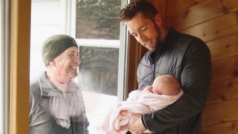 This grandfather walks four miles to see his newborn granddaughter through a glass door.