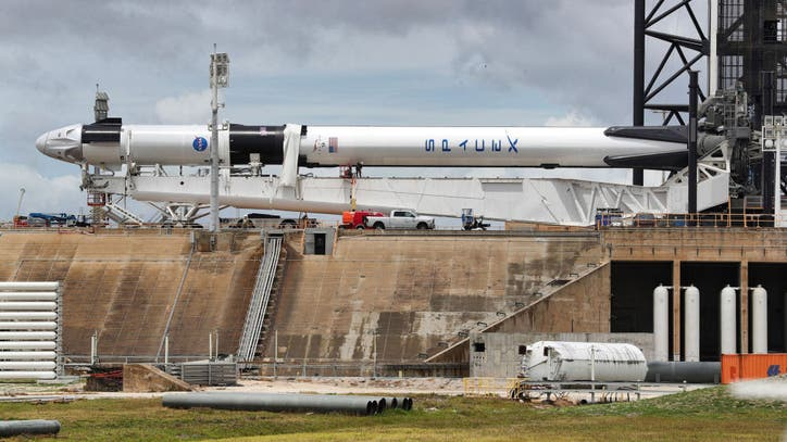 2 U.S. astronauts board SpaceX rocket for historic...
