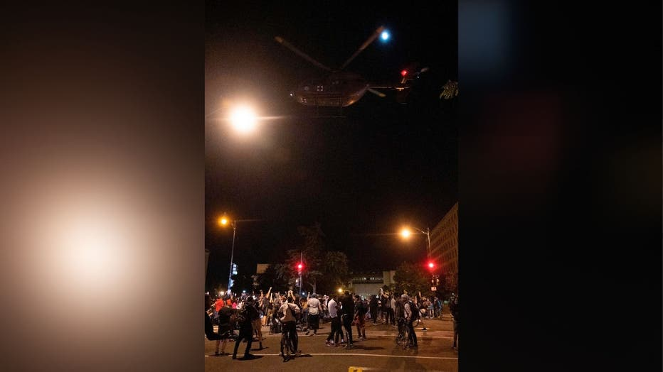 Helicopter flies over protesters