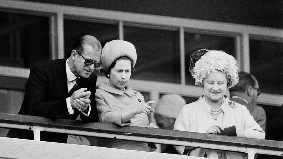 FILE - Prince Philip, Duke of Edinburgh, Queen Elizabeth II, and Queen Elizabeth, the Queen Mother watch the racing on Derby day at Epsom Downs race course in June 1967. (Photo by Victor Blackman/Express/Hulton Archive/Getty Images)