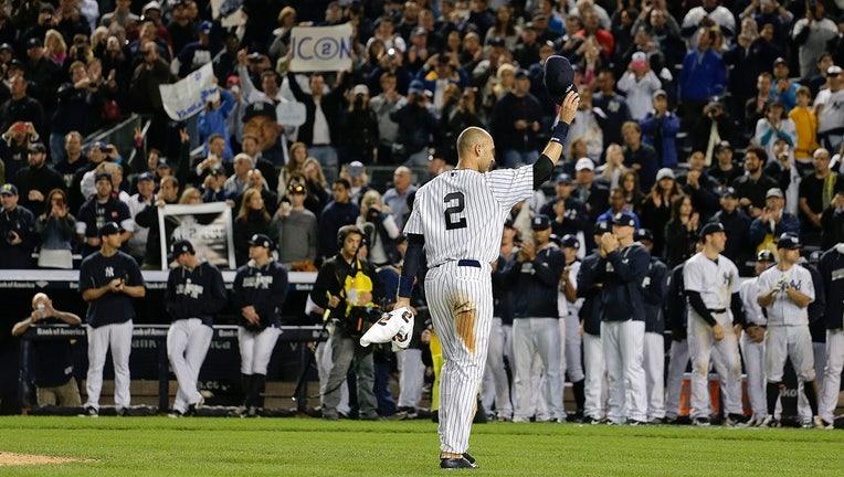 Derek Jeter, wearing pinstripes, waves to fans at Yankee Stadium