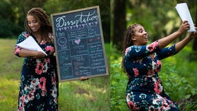 'I make mom cry': Woman poses with dissertation in 'baby' photo shoot to celebrate doctorate