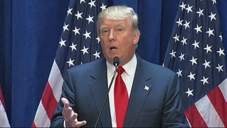Donald Trump speaks into a microphone with American flags behind him