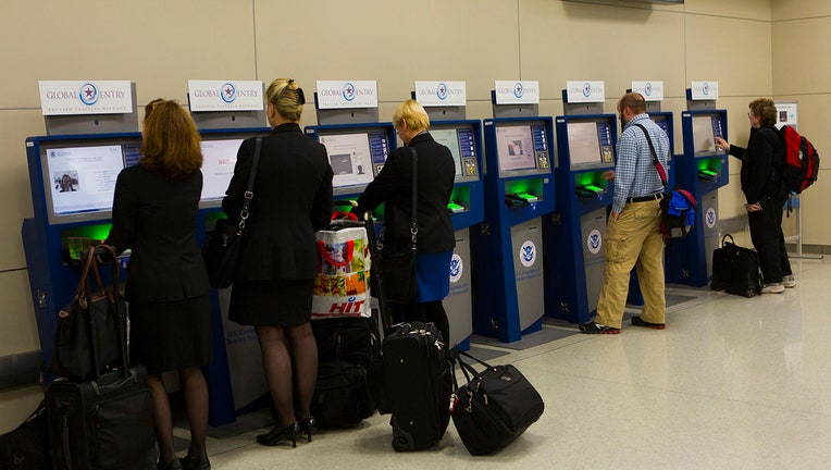 Travelers using Global Entry kiosks.