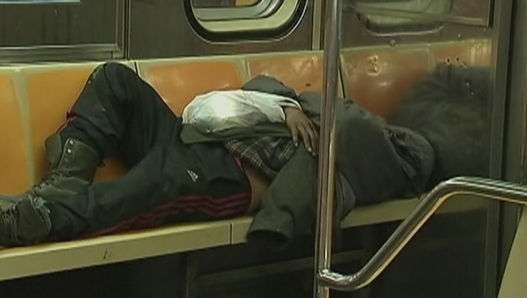 An indigent person sleeping on some seats in a subway car