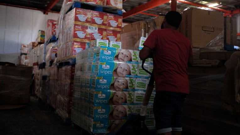 A man removes diapers and baby wipes from a warehouse filled with supplies, believed to have been from when Hurricane Maria struck the island in 2017, in Ponce, Puerto Rico on Jan. 18, 2020. (Photo by RICARDO ARDUENGO/AFP via Getty Images)