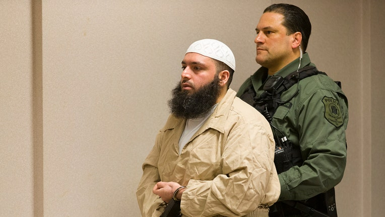 A corrections officer escorts Manhattan bomber Ahmad Khan Rahimi, in handcuffs, into a courtroom
