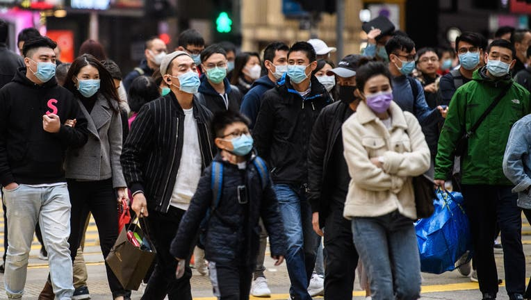 Pedestrians wearing face masks cross a road during a Lunar New Year of the Rat public holiday in Hong Kong.
