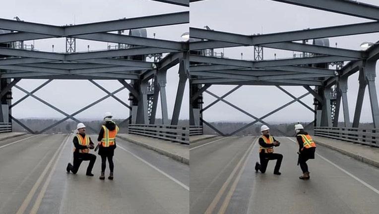 Kneeling man proposes to woman on a bridge