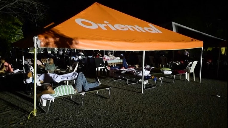 Residents rest on cots under a tent