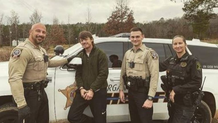 Heath Swafford poses with deputies who have just arrested him. (Morgan County Sheriff's Office)