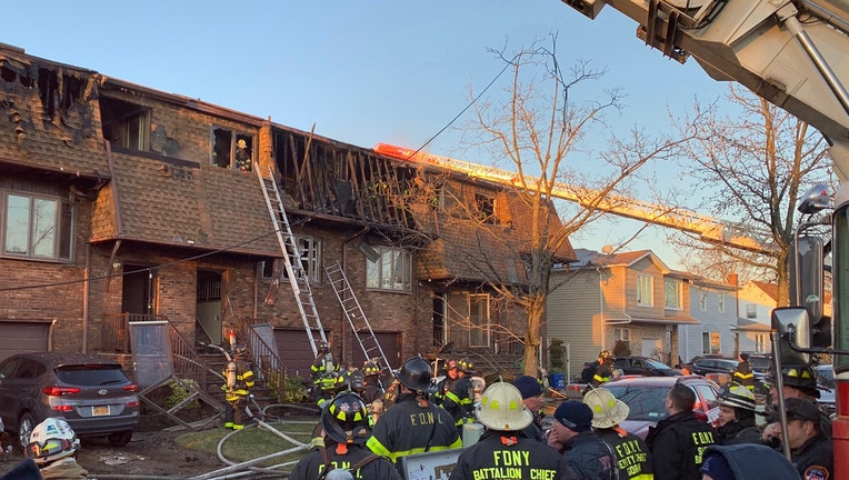 Firefighters outside a row of homes burned in a fire