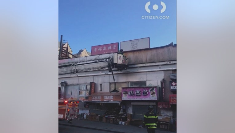 Firefighters examine building facade