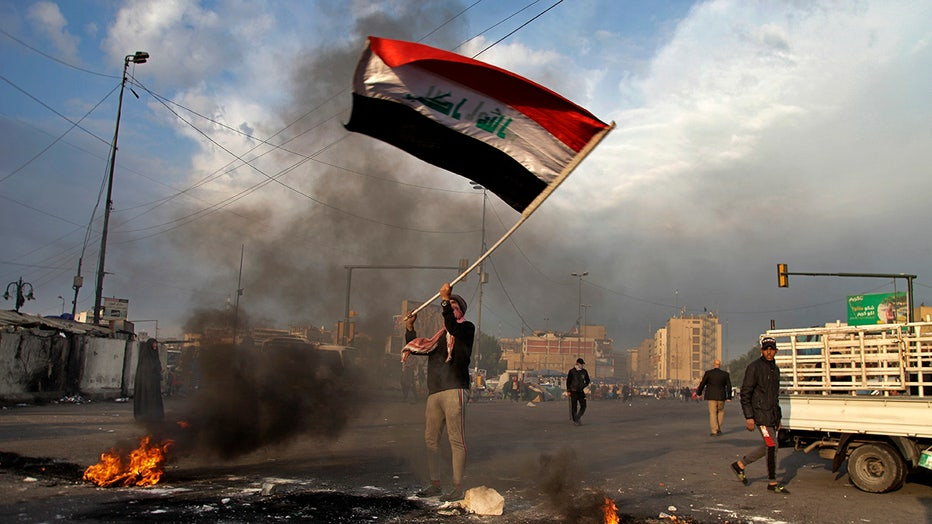 A protester waves the national flag in Baghdad, Iraq