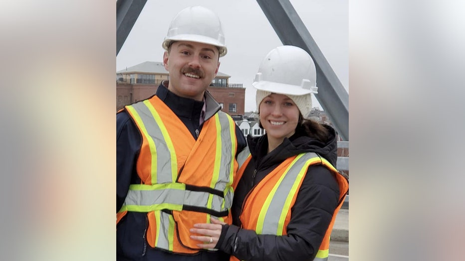 Man and woman wearing hardhats and safety vests smile