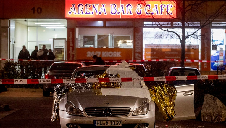 A car with dead bodies stands in front of a bar