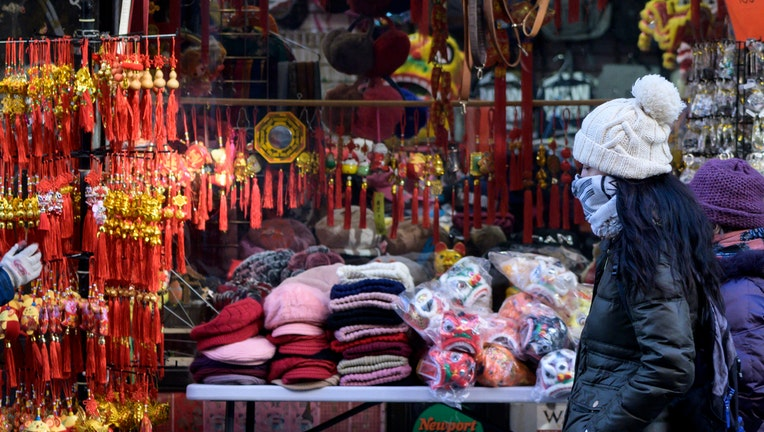 People wear masks as they walk through New York's Chinatown in New York City on February 14, 2020. (Photo by Johannes EISELE / AFP) (Photo by JOHANNES EISELE/AFP via Getty Images)