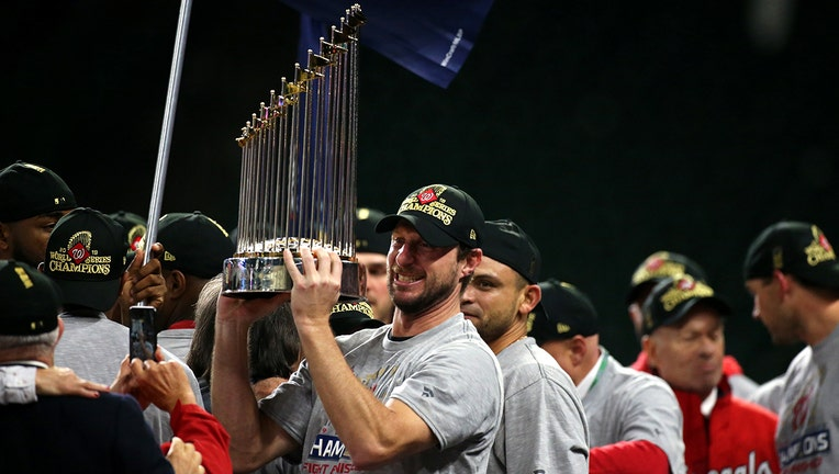 Baseball players and World Series trophy