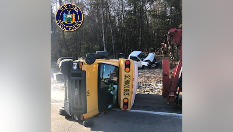 A yellow school bus on its side on the road and a damaged white pickup truck in the background