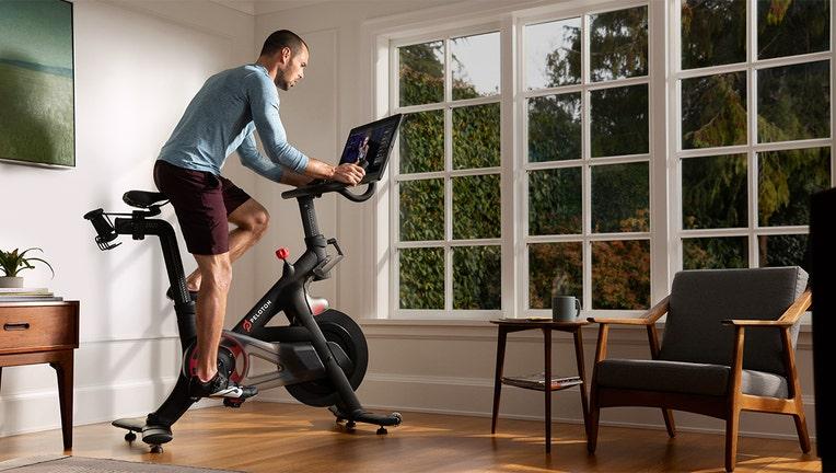 A man rides a Peloton exercise bike