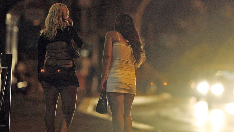 sex workers stand on a street as a car approaches
