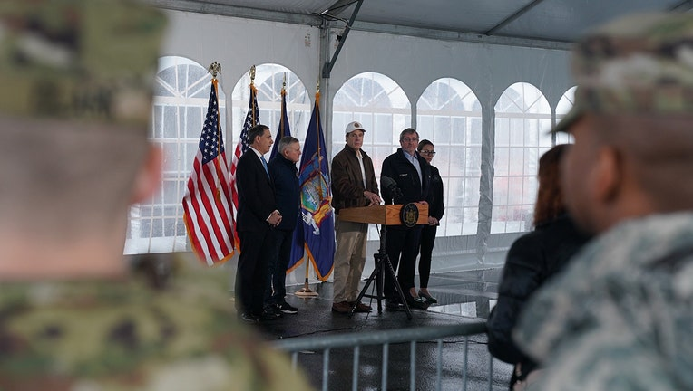 Cuomo and others making an announcement in a tent