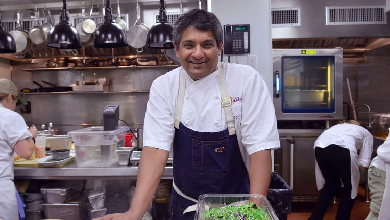 Chef Floyd Cardoz smiling in a kitchen