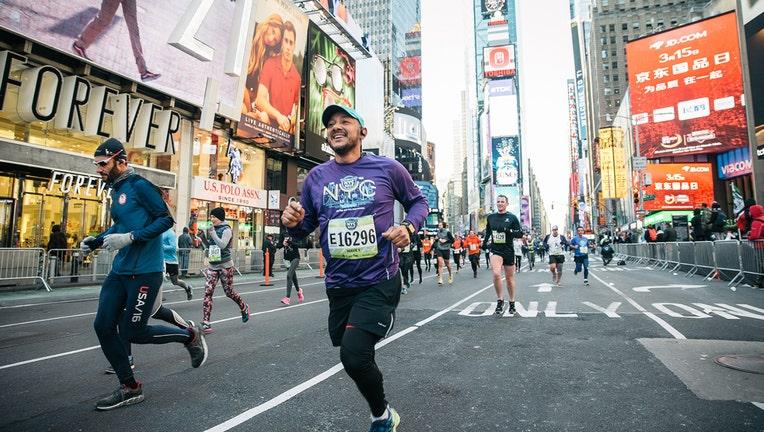 A smilling runner runs through Times Square