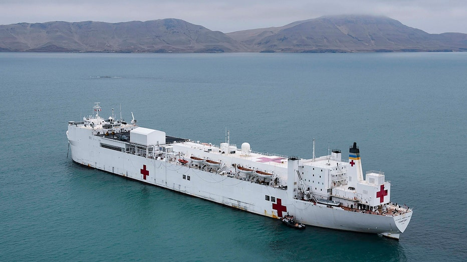 Navy hospital ship Comfort with white hull anchored off Peru with coast and mountains behind it