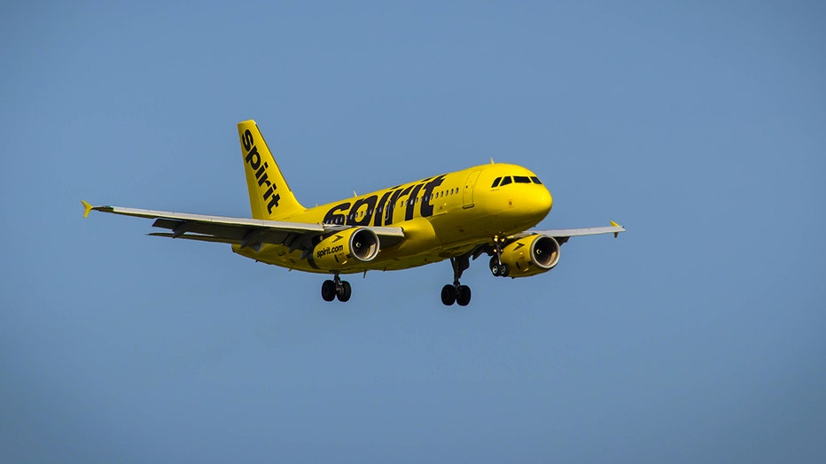 A Spirit Airlines Airbus A319 flying against the backdrop of a clear blue sky