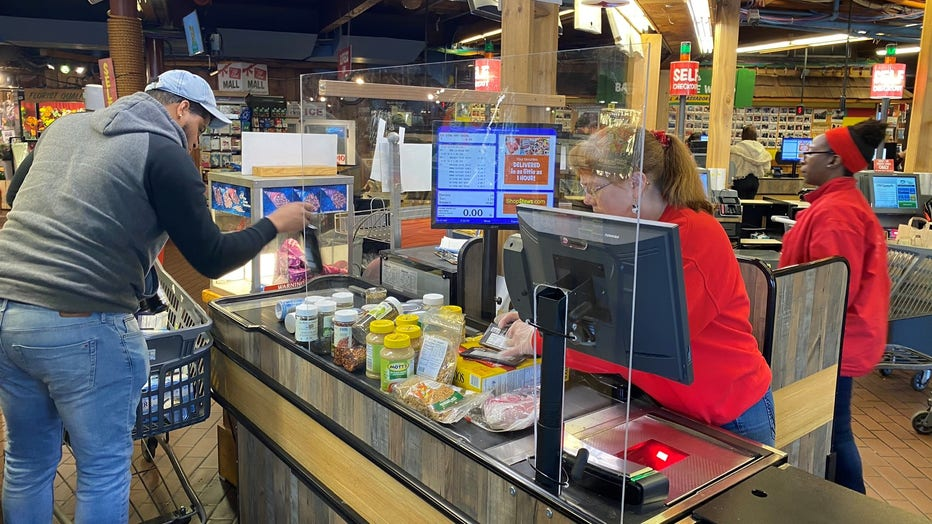 A transparent protective barrier separates the cashier from the shoppers at a Stew Leonard's supermarket.