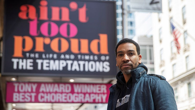 E. Clayton Cornelious with the marquis of a Broadway show behind him