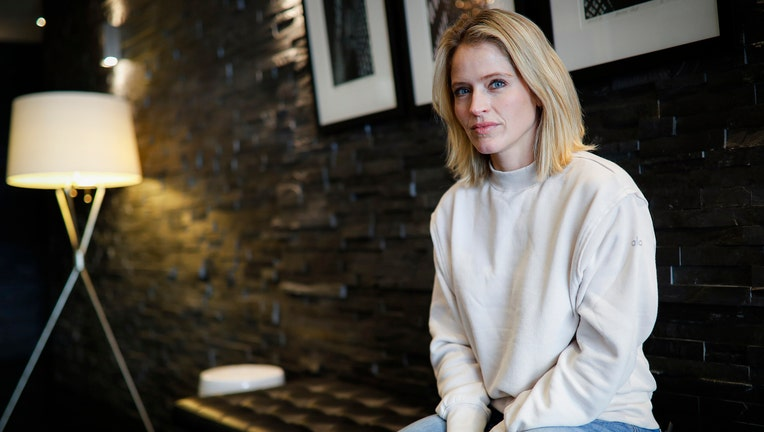 Sara Haines sits on a bench in her lobby