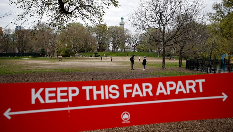 Red and white sign with Fort Greene Park in background