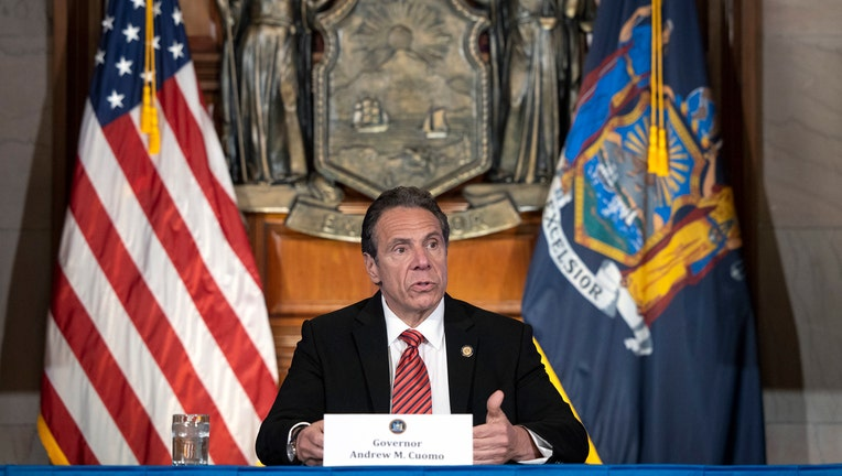 Andrew Cuomo speaks from behind a table
