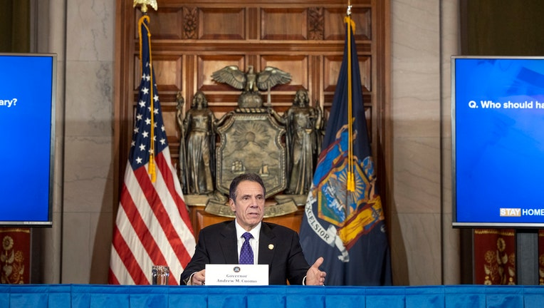 Gov. Andrew Cuomo speaks from behind a desk in Albany with U.S. flag and New York flag behind him
